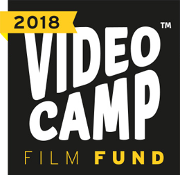 Videocamp Film Fund 2018 logo, consisting of a square black background with VIDEO CAMP written in white capital letters that nearly fill the entire box. The font size for VIDEO is large on the left, and tapers off to the right. The font size for CAMP is large on the right, and tapers off to the left. In the upper lefthand corner, a yellow bar contains the word Edital written in black. On the bottom, underneath the title, DE FILMES 2018 is written in yellow capital letters with the year in bold.