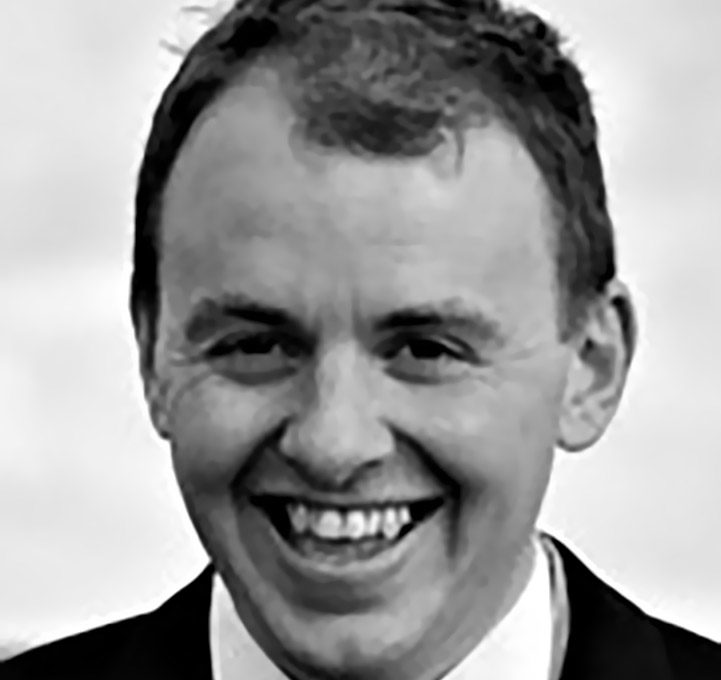 Black-and-white photo with Andrew in the foreground. He is a light-skinned man with small, smiling eyes, hair brushed sideways, and a receding hairline. He's wearing a black suit over a white shirt and tie.