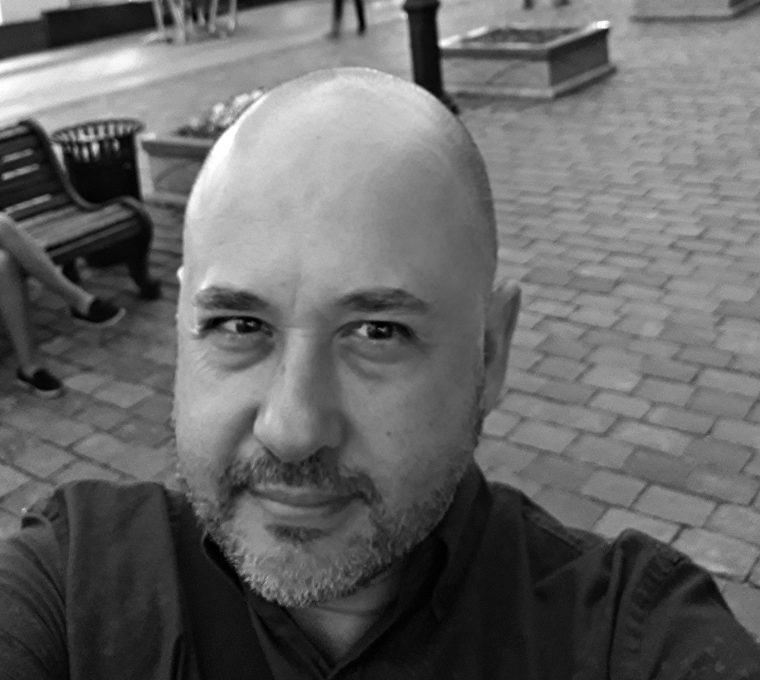 Black-and-white selfie of a bald white man looking directly into the camera and wearing a dark shirt. In the background is a street with out-of-focus lampposts, shops, banks, and passersby.
