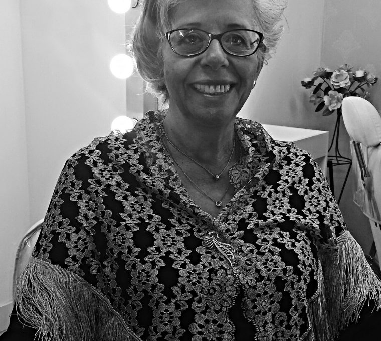 Black-and-white upper body shot taken in a dressing room, with three lamps on the right and a vase of synthetic flowers and a chair on the left. In the foreground, a white woman with short gray hair is looking directly into the camera and smiling. In addition to 2 pendant necklaces, she's wearing glasses, and a dark long-sleeved shirt under a light lace shawl with a brooch.