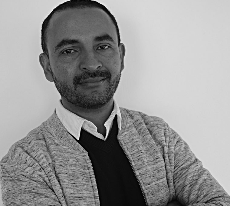 Black-and-white photo with Raul in the foreground. He is a black man with short black hair, a big forehead, thick eyebrows, and trimmed mustache and beard. Wearing a gray jacket over a black sweater and white shirt, his arms are crossed and he's giving a faint smile.