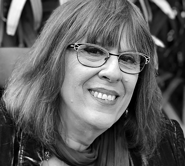 Black-and-white upper body shot of a white woman with straight, shoulder-length hair and glasses. She's smiling at the camera, and is wearing a light scarf around her neck and an unbuttoned velvet coat. In the background are out-of-focus leaves.
