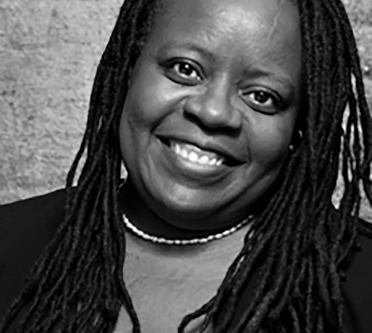 Black-and-white upper body shot, with a background of out-of-focus light-colored bricks, of a black woman with long dreadlocks, looking directly into the camera and smiling. She's wearing a necklace made of white beads and a dark sweater.